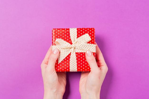 O close-up da mulher entrega guardar a caixa atual do presente no fundo roxo. feriado dia dos namorados