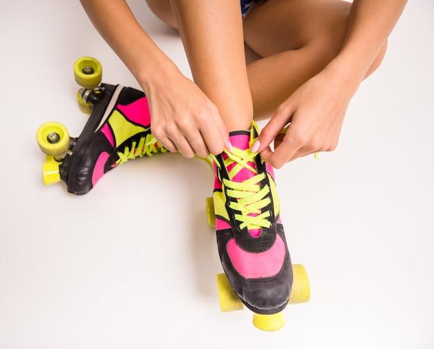 O close-up da mulher nova está desgastando patins de rolo.