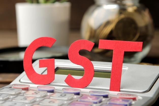 O close-up da palavra gts e calculadora em um fundo de madeira marrom.