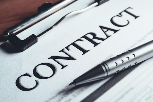 O close-up da pena de prata pôs sobre os papéis do acordo de política do contrato. assinatura de contrato legal.