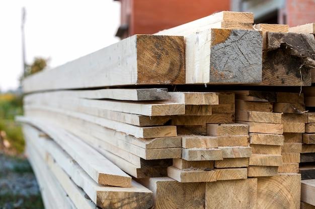 O close-up da pilha empilhada de placas de madeira ásperas desiguais marrons naturais iluminou-se pelo sol brilhante.