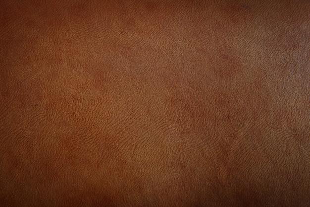 O close up da textura do couro do marrom escuro pode ser usado como o fundo.