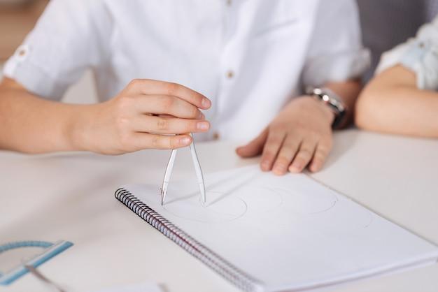 O close-up das mãos delicadas e limpas de um menino sentado à mesa, segurando um par de compassos e inscrevendo círculos