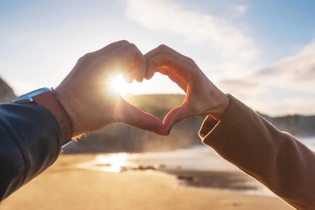 O close up das mãos dos pares que fazem o coração dá forma na praia, na estação do outono. casal feliz no amor.