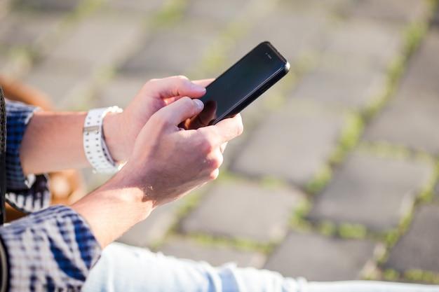 O close up das mãos masculinas está guardando o telefone celular ao ar livre na rua. homem usando smartphone móvel.