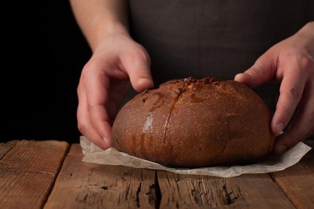 O close up das mãos masculinas põe o pão fresco.