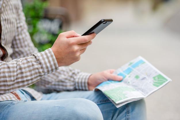 O close up das mãos masculinas que guardam o telefone celular e a cidade traçam fora na rua. homem usando smartphone móvel para encontrar a atração famosa.