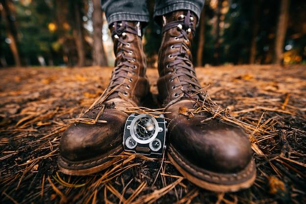 O close up das pernas masculinas nas botas do vintage do moderno que estão no outono moeu com agulhas do pinho.
