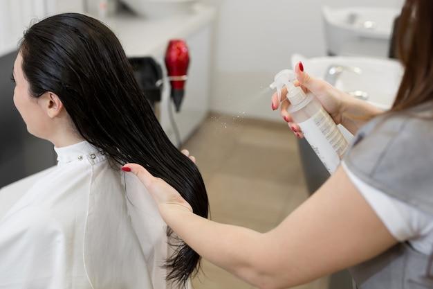 O close-up de barber espirra no spray de cabelo do cliente para facilitar o penteado. procedimento de cuidados com os cabelos no spa. óleo nutritivo, máscara capilar