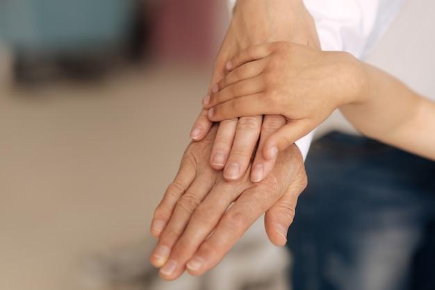 O close up de três mãos de três mulheres, pertencentes a gerações diferentes, sendo colocadas umas sobre as outras com a menor das mãos por cima