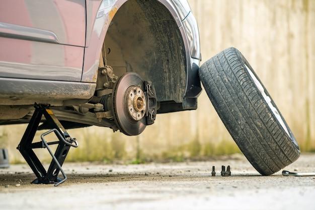 O close up de um carro levantou no jaque em processo da recolocação do pneu da roda nova. avaria de um veículo em uma rua.