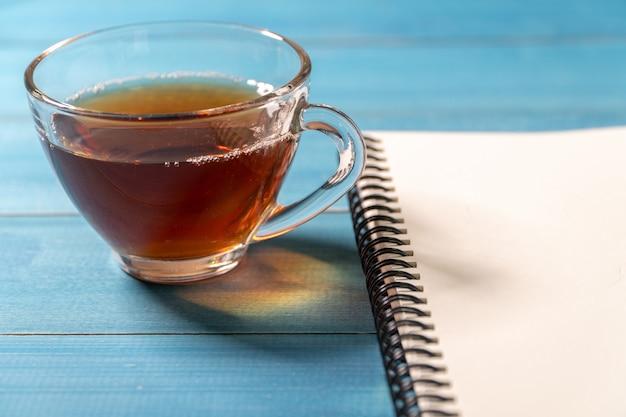 O close up de um copo do chá e o livro vazio puseram sobre uma tabela de madeira azul.