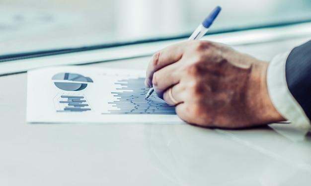 O close up de um empresário é o cronograma financeiro no local de trabalho. a foto tem um espaço vazio para o seu texto