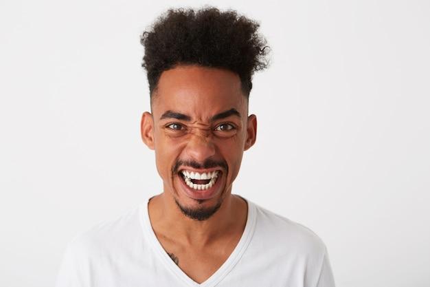O close up de um jovem atraente pensativo com cabelo encaracolado e sardas usa uma camiseta parece pensativo e pensativo isolado sobre a parede branca