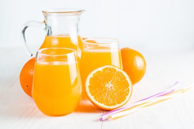 O close-up de um vidro do suco de laranja com laranjas frutifica no fundo de madeira.