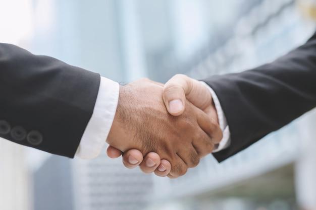 O close up de uma mão do homem de negócios agita o investidor entre dois colegas está bem, sucede no negócio de mãos dadas.