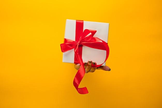 O close-up de uma mão feminina segurando um presente através de um papel amarelo rasgado, isolado