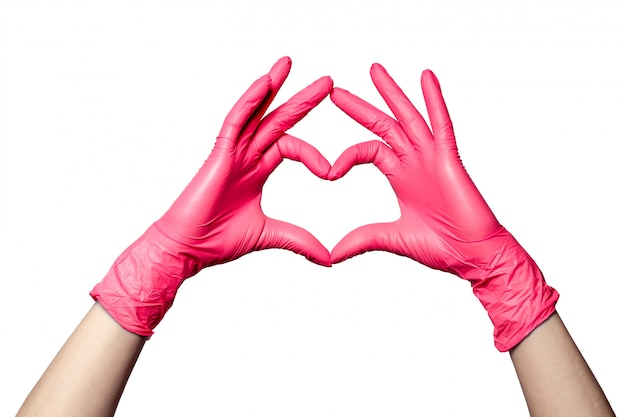 O close up de uma mão nas luvas cor-de-rosa médicas de borracha do látex dobrou-se em um sinal do coração. isolado no fundo branco