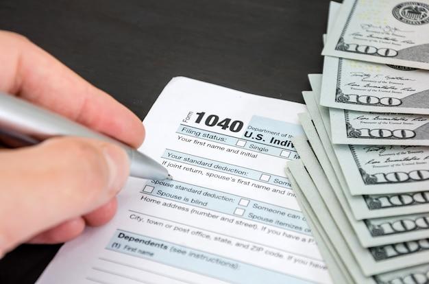 O close up de uma mão preenche formulários fiscais 1040