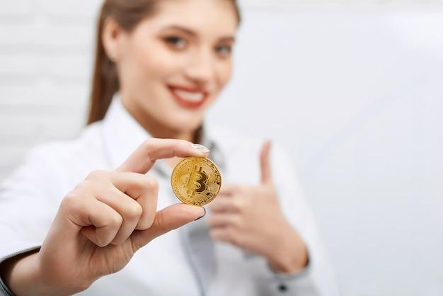 O close-up de uma mulher de negócios consideravelmente nova que veste o vestido-código preto e branco guarda o bitcoin dourado.