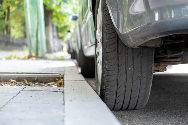 O close up de uma roda de carro estacionou perto do meio-fio no lado da rua em um parque de estacionamento.