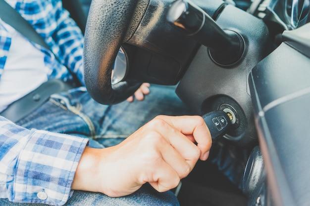 O close up dentro do carro da mão masculina que guarda chave na chave do motor do começo da ignição.