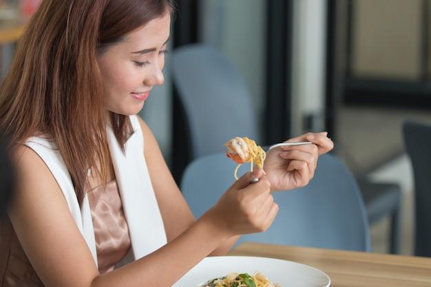 O close up disparou da jovem mulher que come o alimento no restaurante.