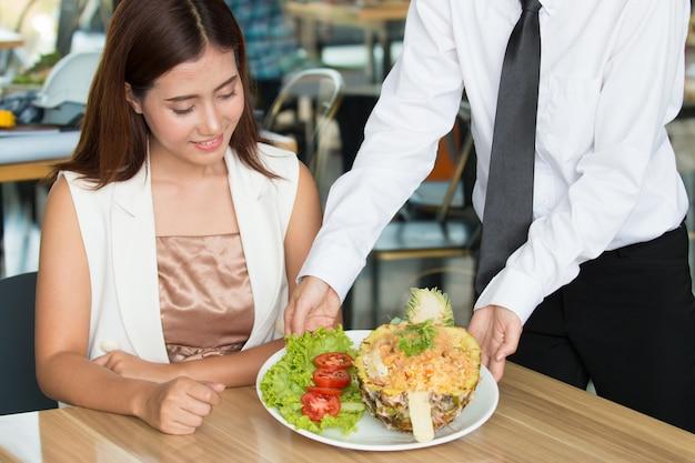 O close up disparou da jovem mulher que come o arroz fritado no restaurante.