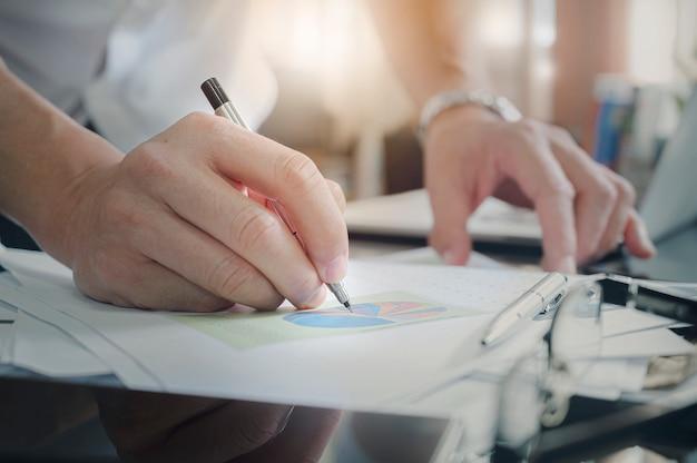 O close up disparou da mão do homem usando a escrita da caneta no documento, carta do gráfico na tabela ao trabalhar no escritório moderno.