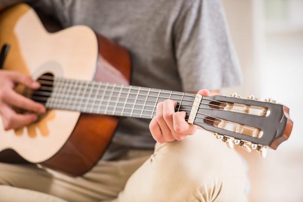 O close-up do adolescente está sentando-se em casa e está jogando-se a guitarra.