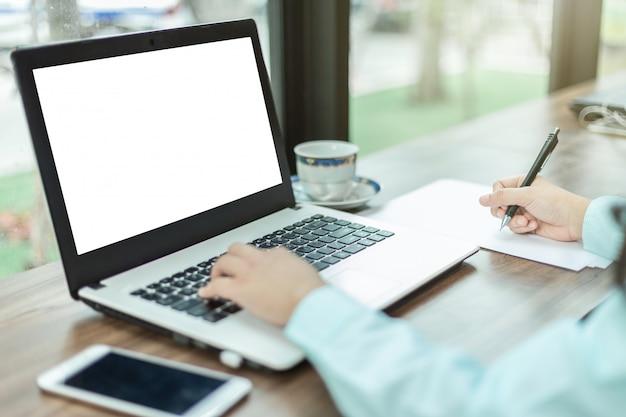 O close-up do funcionamento fêmea do negócio com portátil faz uma anotação na cafetaria como o fundo.
