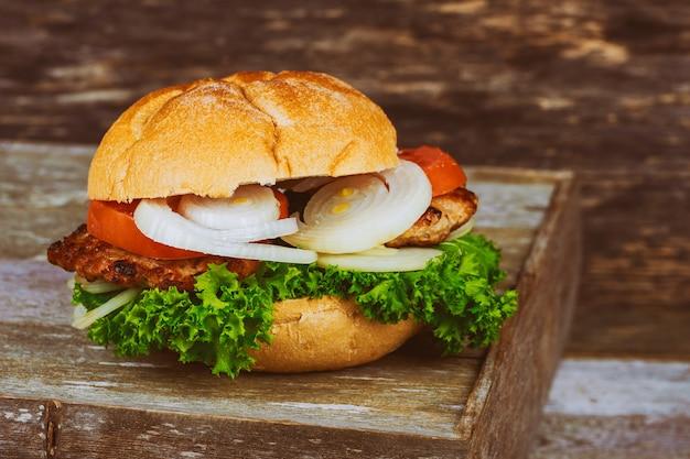 O close up do hamburguer do queijo da casa fez hamburgueres da carne com alface servida em pouca placa de corte de madeira.