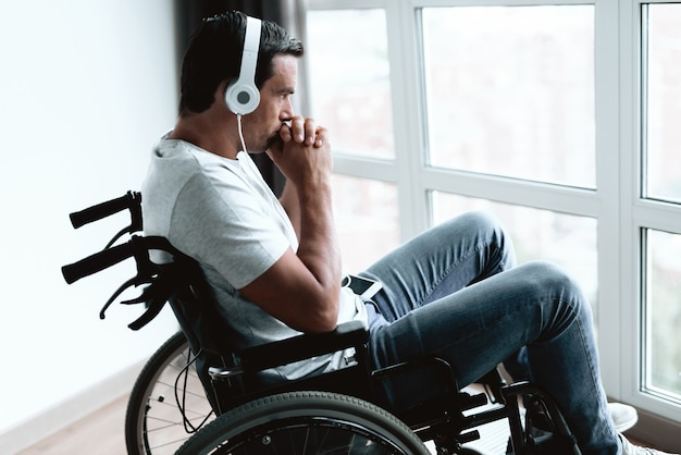 O close up do homem deficiente triste pensa nos fones de ouvido.