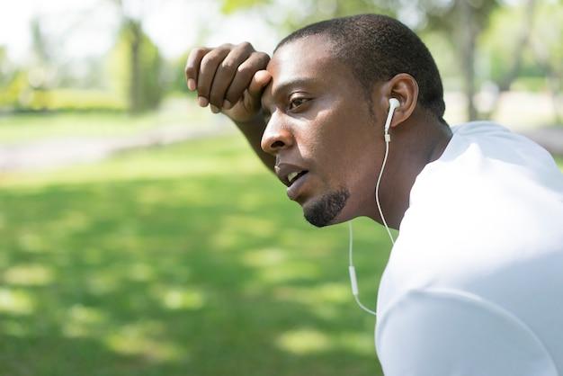 O close up do homem negro cansado esgotado após a manhã corre no parque.