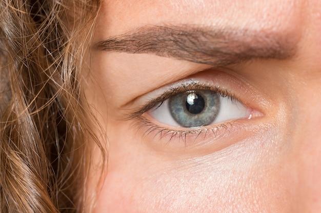 O close-up do olho cinza no rosto de uma jovem e linda garota caucasiana