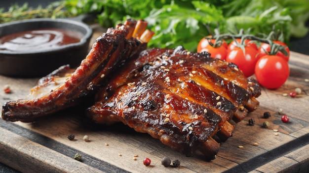 O close up dos reforços de carne de porco grelhou com molho do bbq.