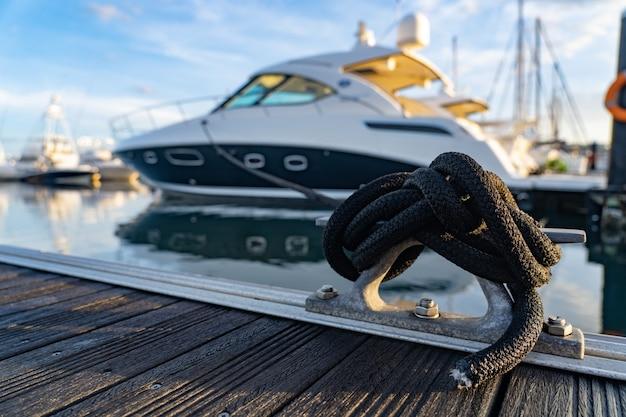 O close up imagina uma corda amarrada a um grampo de metal no convés de um iate com o barco no fundo.