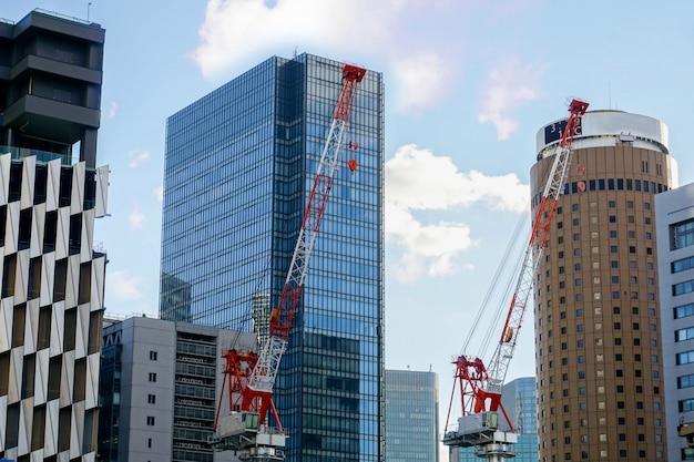 O close up que iça cranes o trabalho na opinião da paisagem da cidade e no prédio de escritórios de vidro com céu azul e fundo sedoso da nuvem.