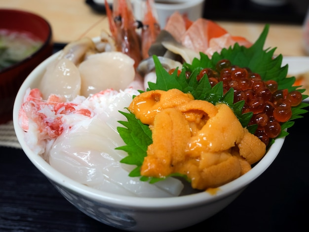 O close up seleciona vários frutos do mar frescos cobertos em uma tigela de arroz no estilo japonês, uni (ouriço do mar), ovas de salmão (ovos), hotate (vieiras), carne de caranguejo e camarões, tigela de arroz japonesa