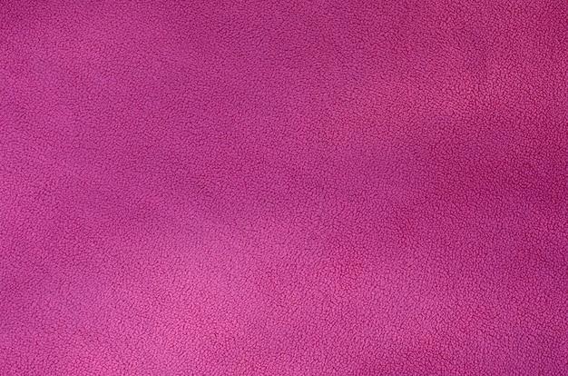 O cobertor de tecido de lã rosa peludo. uma textura de fundo de material de lã de pelúcia macia rosa claro