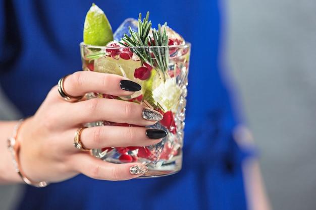 O cocktail exótico e mãos femininas