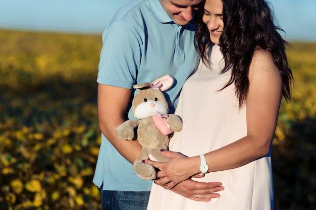 O coelho de brinquedo encontra-se sobre os braços do jovem casal esperando