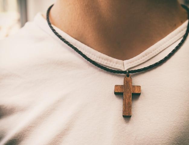 O colar de cruz de madeira no pescoço do homem