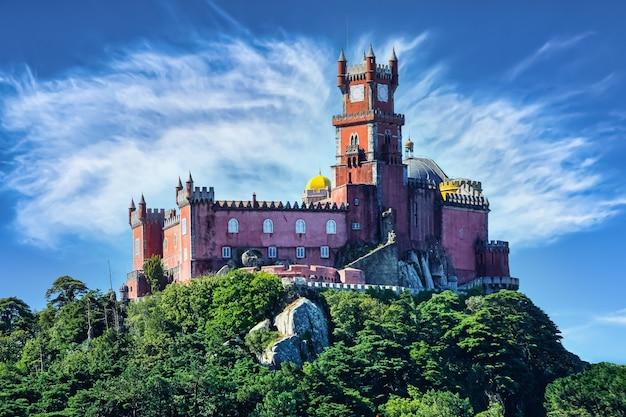 O colorido palácio de sintra localizado no topo de uma colina com céu azul e nuvens.