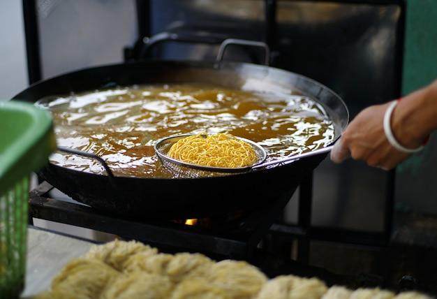 O comerciante frita macarrão amarelo crocante na grelha de fritura em uma panela grande de óleo quente. macarrão de ovo crocante para macarrão em molho grosso estilo comida chinesa-tailandesa.