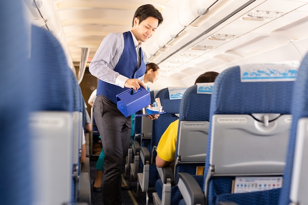 O comissário de bordo da bangkok airways serve bebidas aos passageiros a bordo.