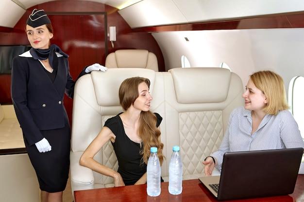 O comissário de bordo está dentro do jato executivo perto dos assentos com passageiros da primeira classe conversando enquanto assistem ao filme no laptop.