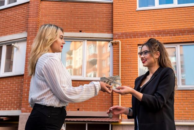 O comprador dá dólares ao vendedor no fundo da casa. comprar ou alugar uma nova casa