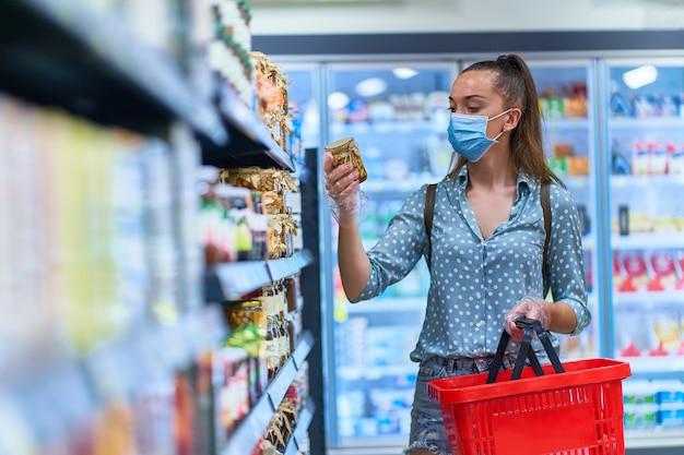 O comprador da mulher em uma máscara protetora com cesto de compras escolhe produtos alimentares em uma mercearia