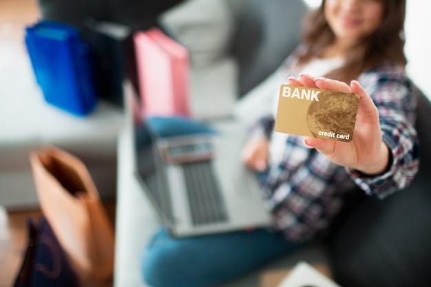 O comprador olha para a tela e possui um cartão de crédito. uma jovem usa um laptop para comprar muitos produtos on-line.
